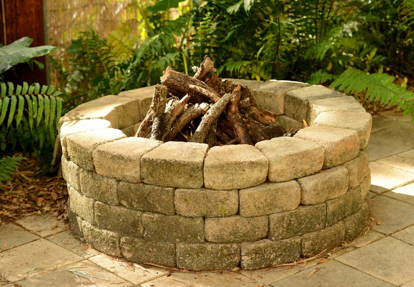 stone fire pit with bricks in the backyard